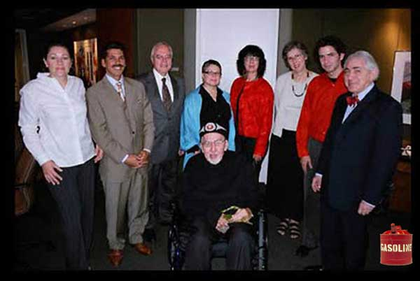 "An early founding photo of the NMHS and Norval's white business partners around his wheelchair. On the right is his lawyer, Aaron Milrad who said in an interview in 2005, the group was prepared to ""destroy"" fakes they found objectionable, and would be protected from fall-out by waivers he would get collectors to sign before they submitted paintings for ""evaluation."" We believe that may explain the gas can behind him."