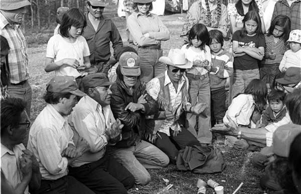 "Traditional Chipewyan ""hand-games,"" during a three day wedding celebration, in a remote bush camp miles from the village, in 1977. Left to right: Pierre, Little Joe, Fred, Tommy, Georgie, with Moise, looking on. Life in the bush was almost always alcohol free. Nobody boozed - booze was entirely a town (not bush) and a social (not private) activity - as people connected to their traditional tribal - alcohol free - roots with a passion. Unlike in white society, where teenage drinking binges are notoriously carried out in ""bush"" raves on farms, and fishermen, hunters, and campers routinely connect going into the outdoors to drink - a lot. And TV ads try to burn, into the public consciousness, the message - both overt and subliminal - about going outdoors to drink suggesting: take your fishing rod, your rifle, your tent, but for God's sake, don't forget the booze... (That's me, the school principal on the left, the way I always preferred to be, unobtrusive, non-interfering, observing, and learning. I went on hunting expeditions or bush picnics with all the players, and knew every kid in the photo by name. After three years here, the Chief and council petitioned the Department of Education to keep us - my teacher wife Joan above - there. We signed on for another year...)"