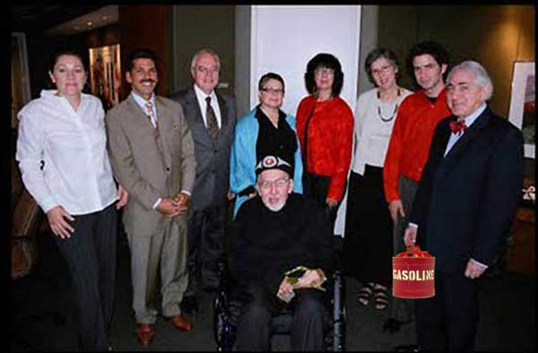 "THEIR MEAL TICKET TO FAME & FORTUNE - A notorious photo of the NMHS and Norval's white business partners, as they circle around his wheelchair. On the right is Gabe Vadas' lawyer, Aaron Milrad who said in an interview, in 2005, that the group was fully prepared to ""destroy"" so-called fakes they found objectionable. That he would protect NMHS members from legal liability and any negative fall-out by crafting waivers that he would get collectors to sign before they submitted paintings for ""evaluation."" His idea of ""evaluation"" we believe, may explain that ominous looking gas can behind him. They all pretend to be ""serving"" Norval - whose mind is already in the spirit world - when in fact they are all serving Gabe and his wife Michele on the far left. Gabe, a white guy, has been using Norval's Power of Attorney since Apr. 24, 1990, to run a malicious swath of destruction through Canada's Aboriginal art heritage. On display are all his enablers. A notable collaborator is the National Gallery of Canada's Greg Hill in the red shirt."