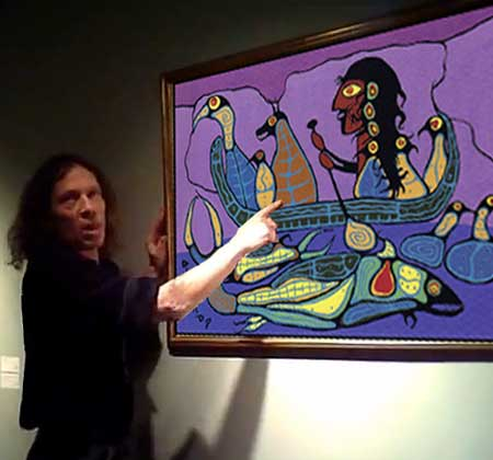 Ritchie Sinclair performing in a video for Kinsman Robinson Galleries. On the wall Sinclair is pointing to one of five fakes he accused Norval and KRG of publishing in Tral